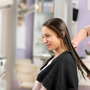 Hairdresser combing womans hair in salon