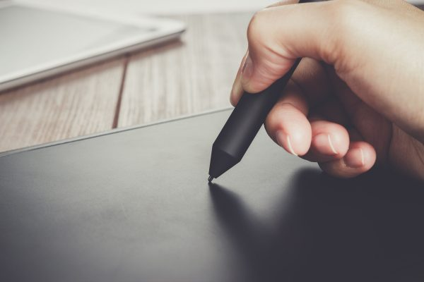 hand of the designer with pen on tablet