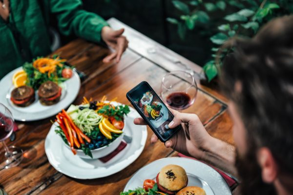 Man Photographing Food In A Restaurant