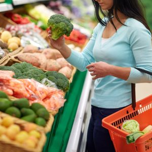 woman with basket buying broccoli at grocery store